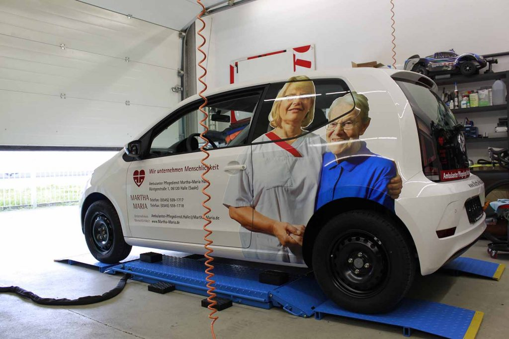 Auto folieren, Autofolierung, Autowerbung Fahrzeugwerbung weisser VW up! Martha Maria Flanke, Seite mit Logo, Beschriftung und Bild