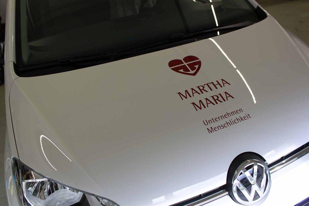 Auto folieren, Autofolierung, Autowerbung, Fahrzeugwerbung, weisser VW up! Martha Maria Motorhaube mit Beschriftung und Logo